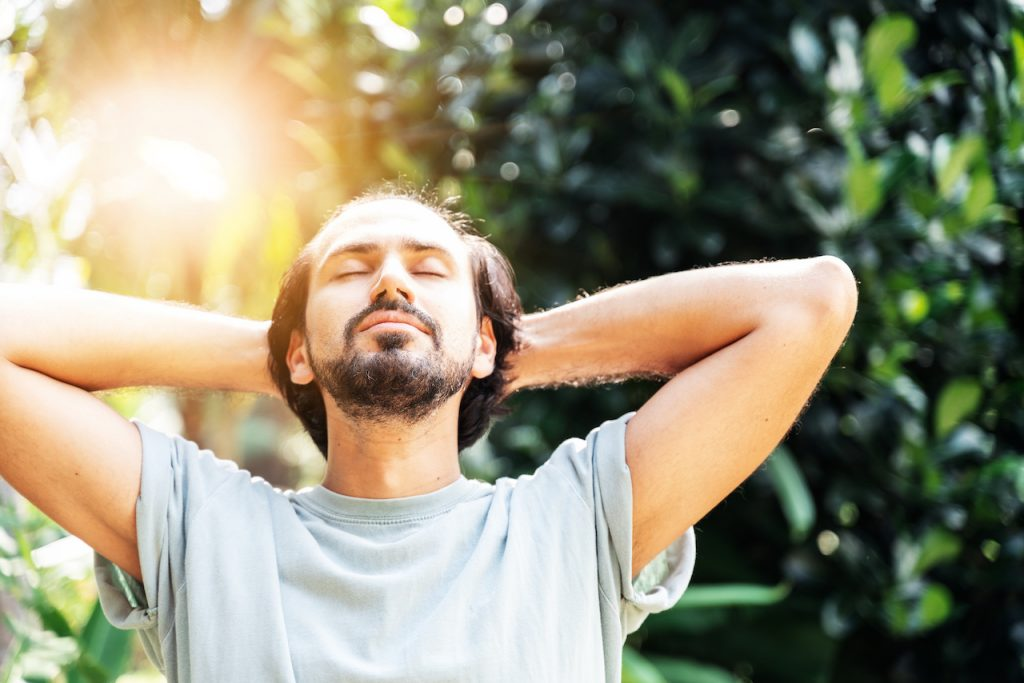 A bearded man is meditating outdoor in the park with face raised up to sky and eyes closed on sunny summer day meditating