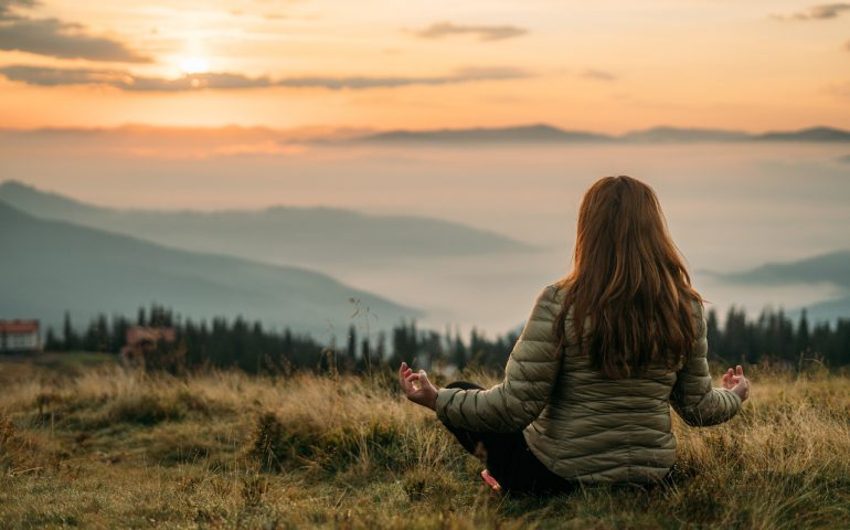 yoga girl exercises on sunrise meditation in the autumn mountains