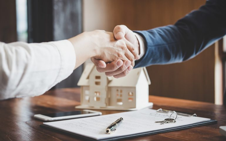 Real estate agent and customers shaking hands together celebrating finished contract after about home insurance and investment loan, handshake and successful deal.