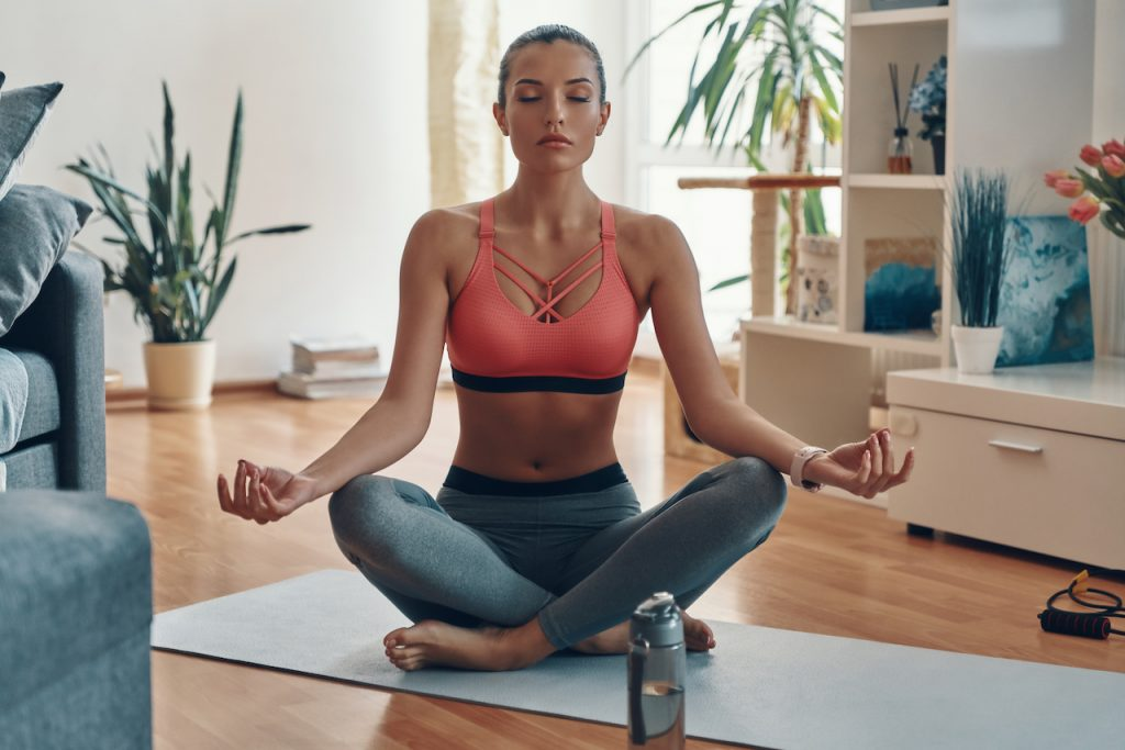 Woman learning how to meditate in lotus position.