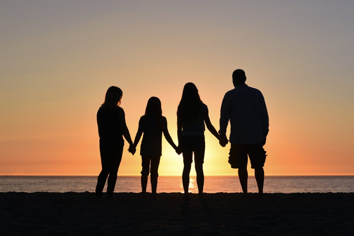 Family of four holding hands, family at a beach in sunset