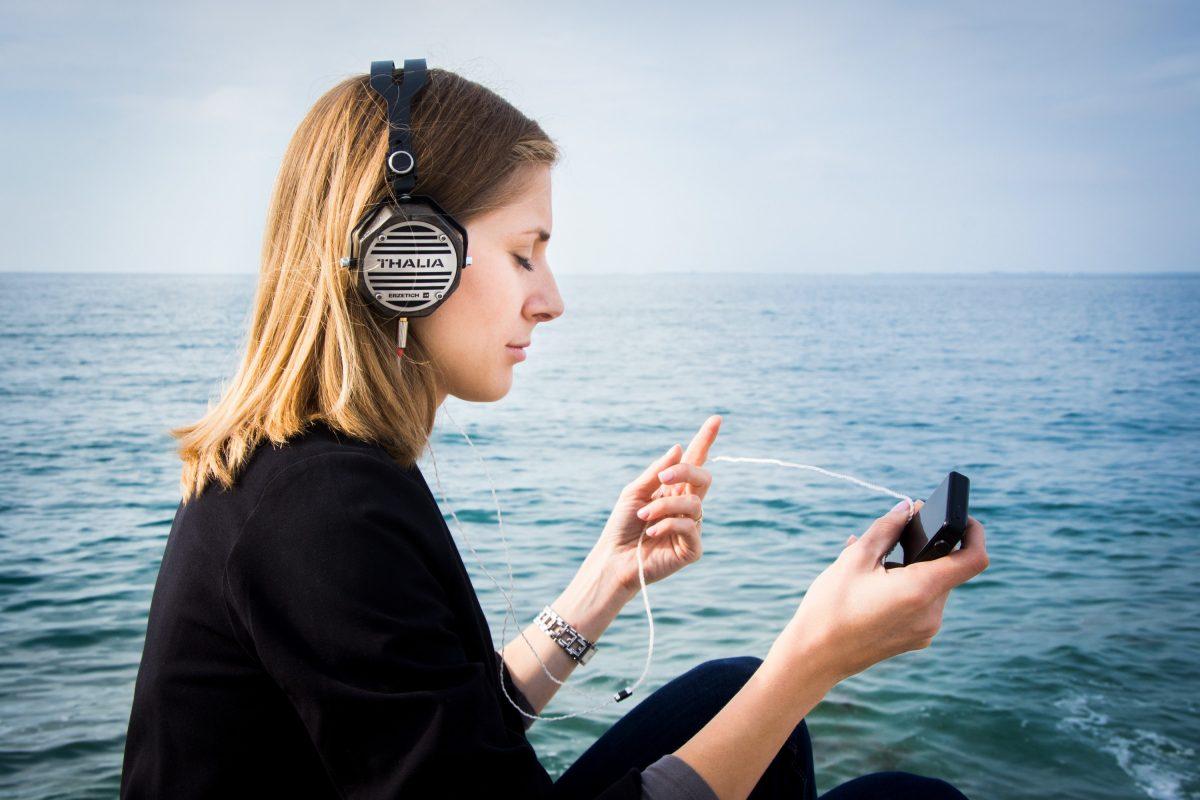 woman choosing music near the sea