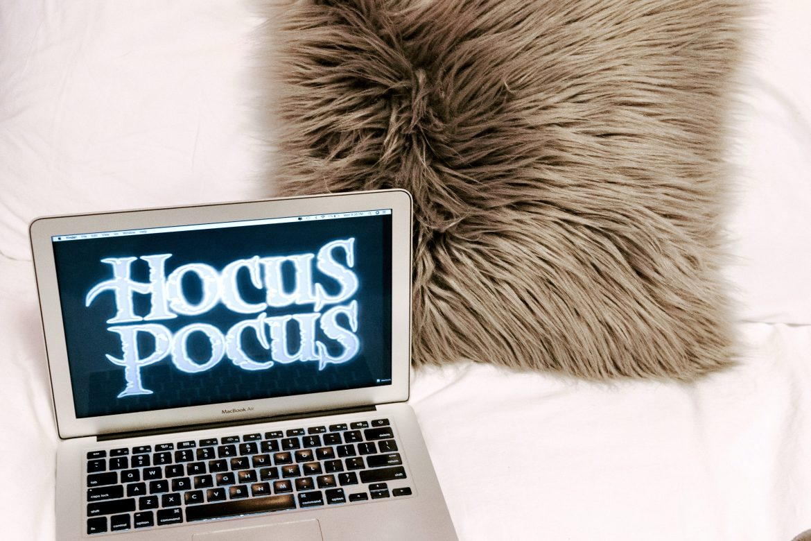 halloween movies playing on laptop placed in bed