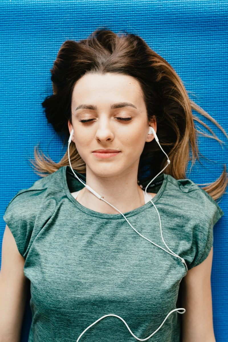 woman with eyes closed listening to music on earphones