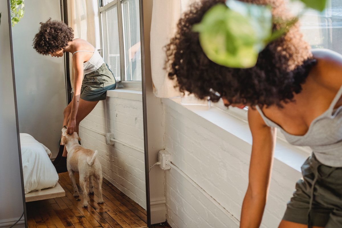 woman petting dog in front of a mirror
