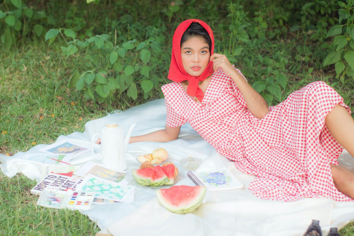 Woman wearing a red and white goblincore outfit having picnic outdoors