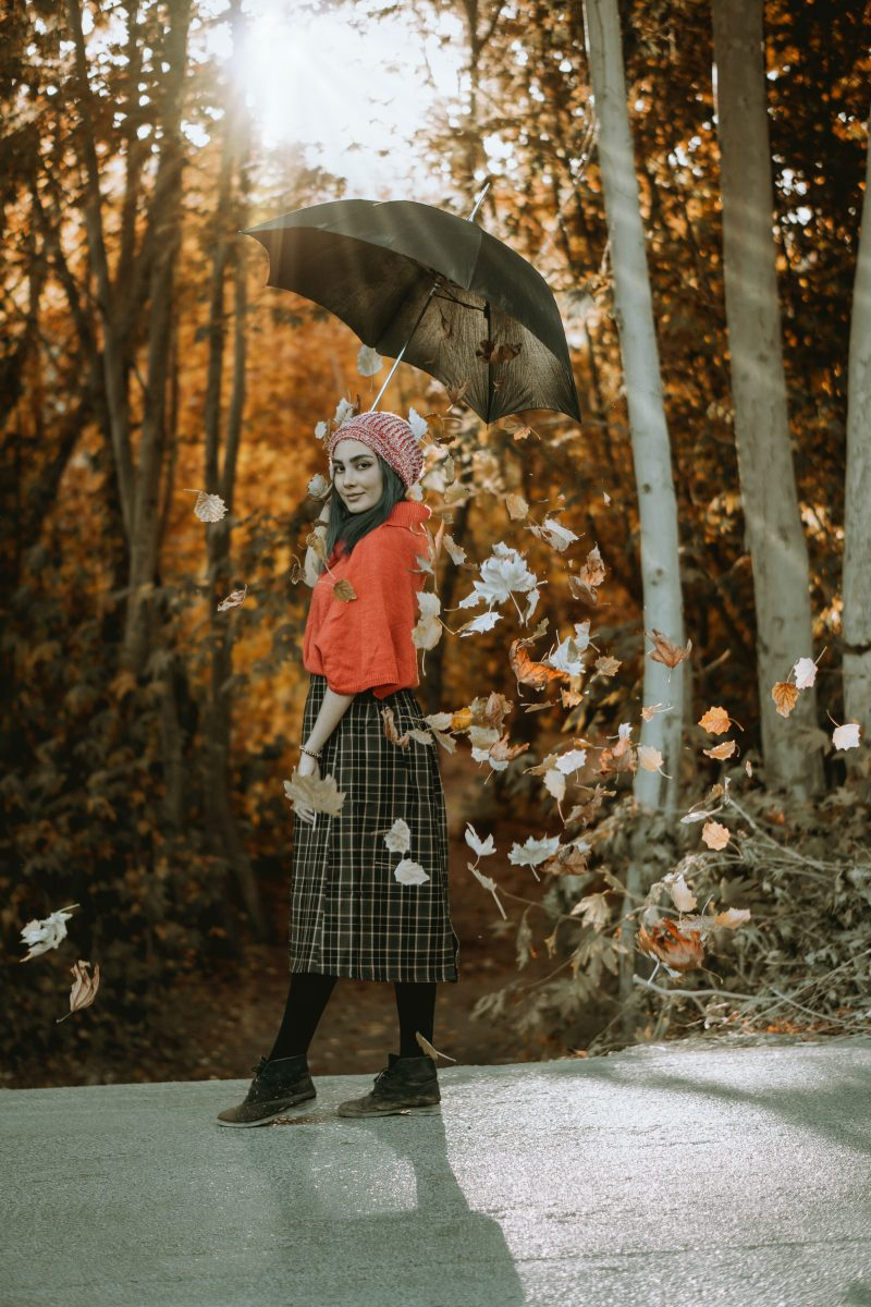 Woman in nature wearing a goblin-inspired outfit and holding a black umbrella
