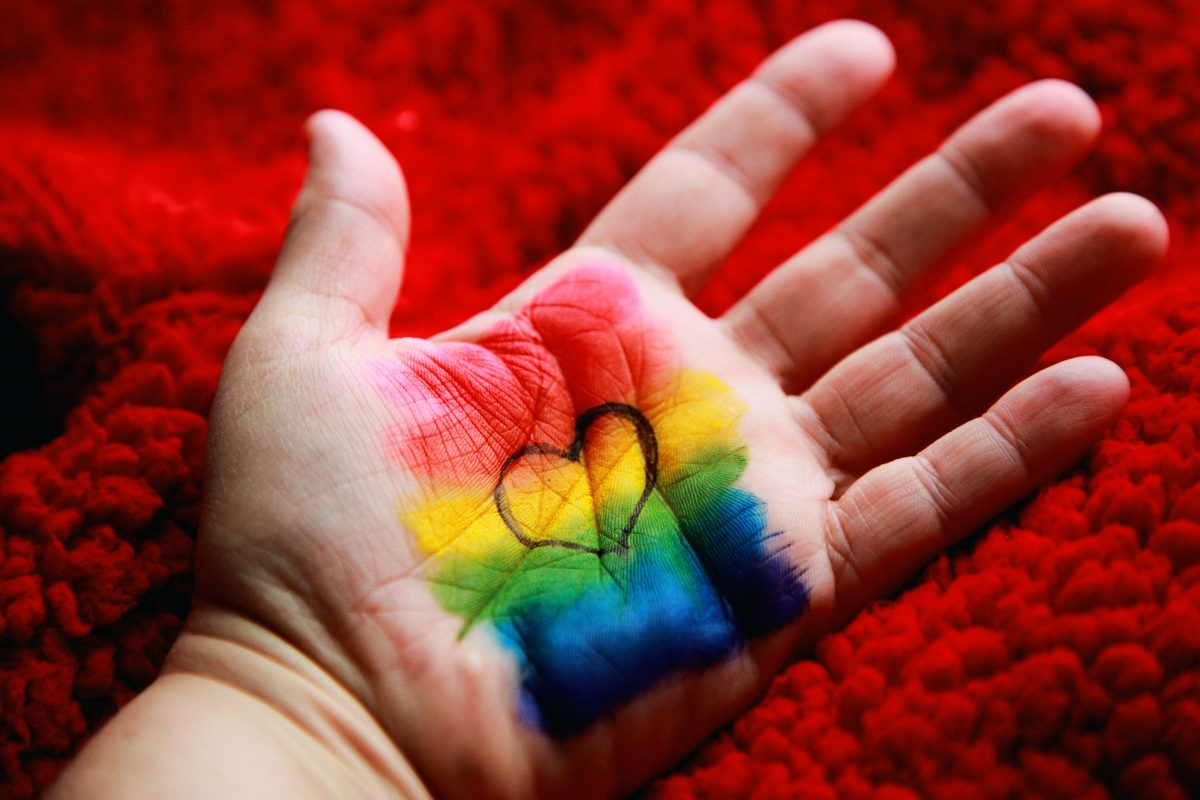 Heart doodle against a rainbow-painted palm