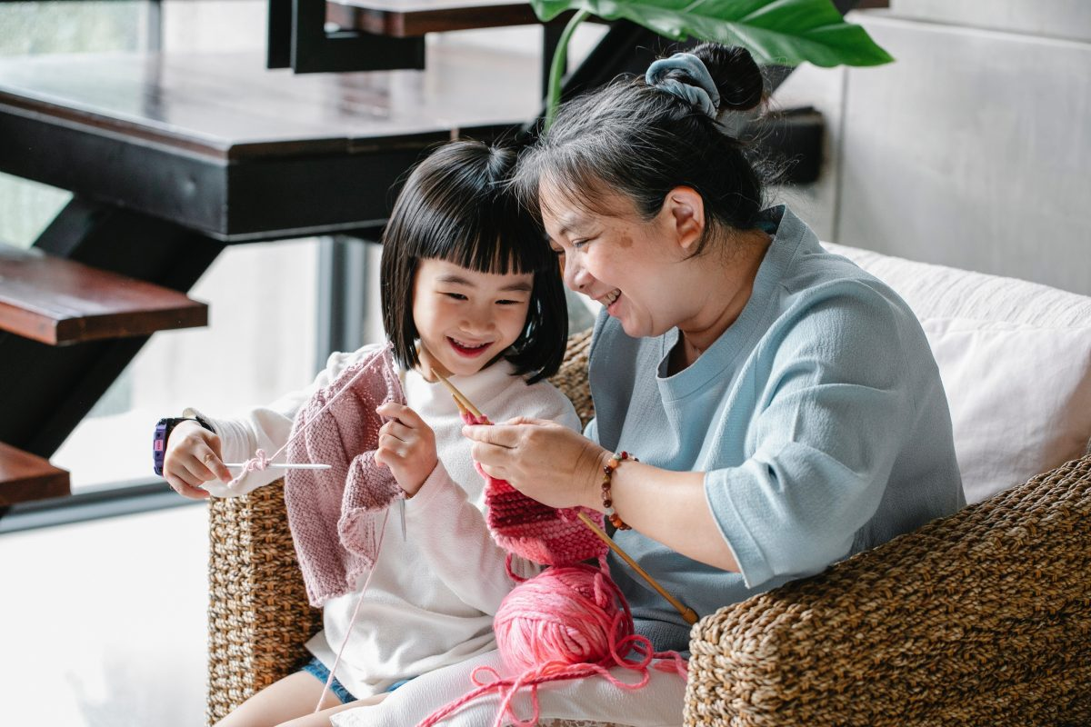 Smiling child and grandmother knitting together