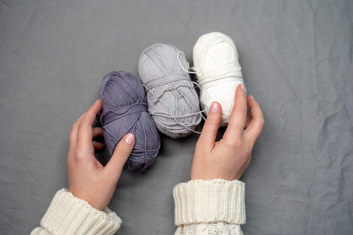Person holding three yarn rolls for crochet